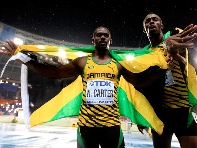 Usain Bolt of Jamaica poses with Nesta Carter in 2013.