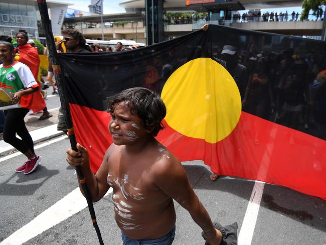 A young indigenous boy carries a spear as demonstrators march through central Brisbane to protest what they call 'Invasion Day'. Picture: AAP