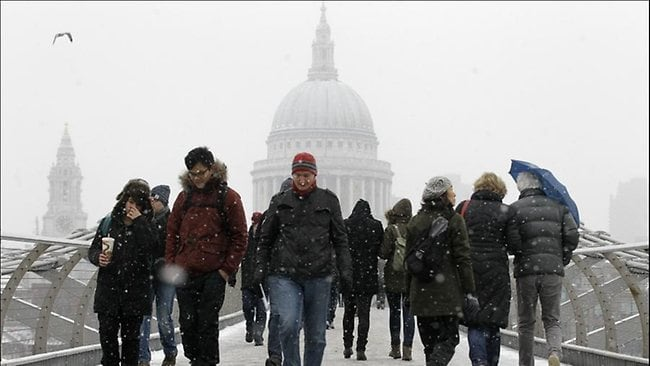 Backdropped by St Paul's Cathedral people walk across a snowy Millennium Bridge in London Friday, Jan. 18, 2013. Britain could be hit heavy snow which is expected hit larger areas of Britain and travel companies have warned of widespread disruptions. (AP Photo/Sang Tan)