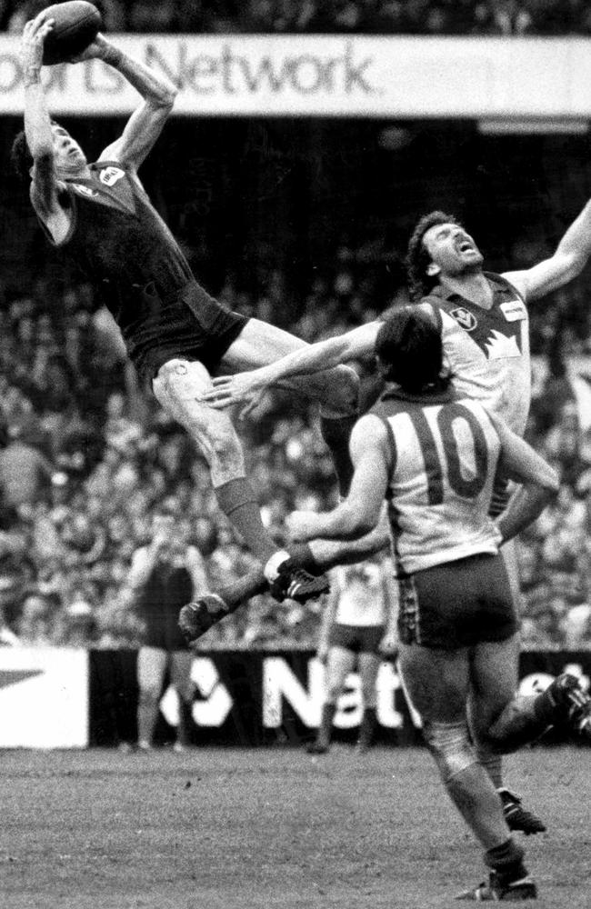 Robert Flower soars over Rod Carter to mark as Barry Mitchell looks on.
