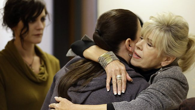 Alexis Somers, center, receives a hug from her aunt, Susan Hare, right, while her sister Rachel MacNeill, left, looks on outside the courtroom during the Martin MacNeill trial. MacNeill and Somers, two of the couple's oldest daughters, have said they believe their father killed their mother.