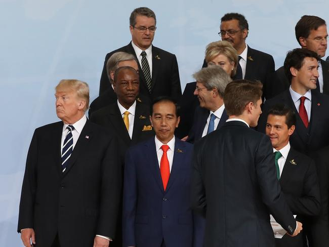 On the outskirts: G20 tradition dictates seniority is a key indicator of where leaders stand. Donald Trump was on the fringe before French President Macron took his place in a picture that seems to underscore his differences on policies such as trade and climate. Picture: Sean Gallup/Getty Images