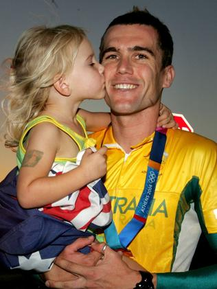 McGee with daughter Tahlia after winning gold in the men's 4000m team pursuit in Athens.