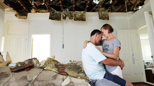 Natalie and Paul Hennessy pictured in their lounge room of the damaged house that will likely be pulled down after a tornado hit the Sydney suburb of Kurnell in December. Picture: Braden Fastier