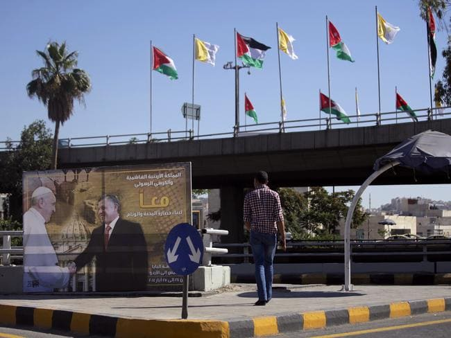 Anticipation for the Pope ... a banner bearing a photo of King Abdullah II of Jordan shaking hands with Pope Francis along with national and Vatican flags adorn the streets hours before the Pope's visit, in Amman, Jordan. Picture: Mohammad Hannon