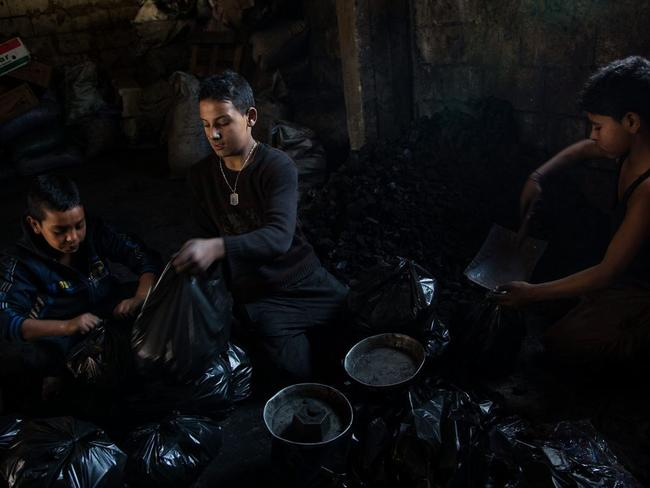 From left to right, Sultan, aged 11, Abdullah and Anas Ezza weigh and pack charcoal into 2kg bags at the charcoal seller's shop in Bebnine. The boys earn 66 cents an hour. On an average day, they start at 8am and finish at 4pm. Picture: UNHCR/ Andrew McConnell
