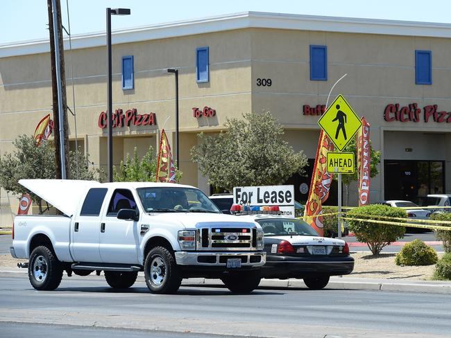 Attack ... Las Vegas Metropolitan Police Department vehicles are parked outside Cici's Pizza where two officers were killed by two assailants. The two suspects then reportedly went into the Wal-Mart where they killed a third person before killing themselves.