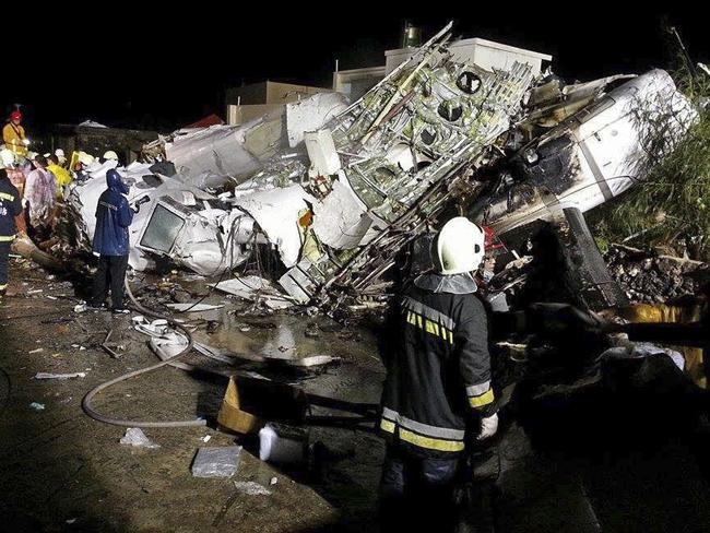 Plane down ... Rescue workers survey the wreckage of TransAsia Airways flight GE222 which crashed while attempting to land in stormy weather.
