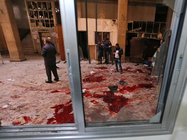Syrian security forces and journalists stand inside the old palace of justice building in Damascus following a suicide attack. Picture: AFP/Louai Beshara
