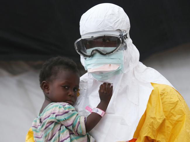Risky work ... A Doctors Without Borders (MSF), health worker in protective clothing holds a child suspected of having Ebola in the MSF treatment centre in Liberia. Photo by John Moore/Getty Images