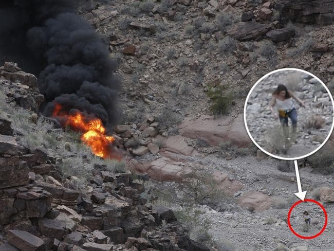 A survivor, lower right, walks away from the scene of a deadly tour helicopter crash along the jagged rocks of the Grand Canyon. Picture: Teddy Fujimoto via AP