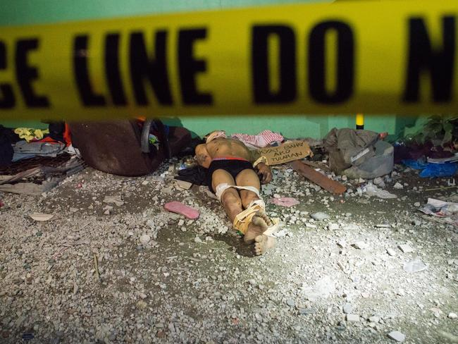 An alleged drug dealer, executed with hands bound and his head wrapped in tape, lies on a road behind police tape in Manila. Picture: Getty Images