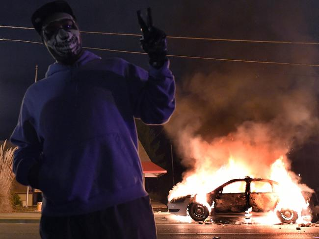 Victory? A demonstrator flashes a sign before a burning police car during clashes between police and protesters overnight. Source: AFP