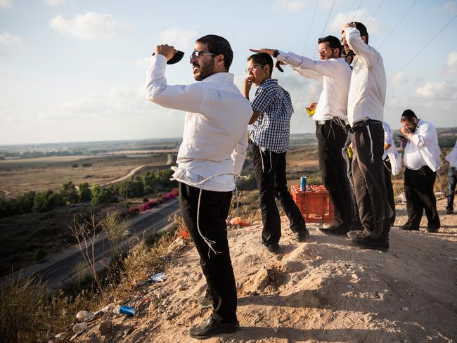 Cheer squad ... Israelis watch for rocket fire from Gaza and wait for Israeli air strikes from a hill overlooking the Gaza strip in Sderot, Israel