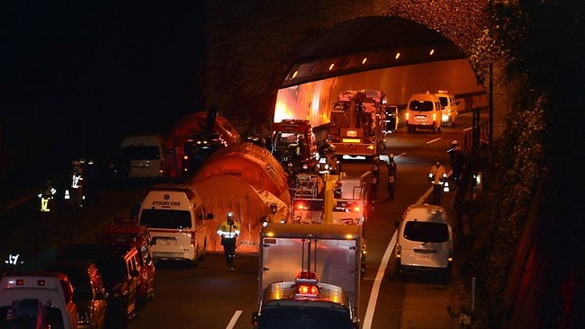 Rescue workers and police outside the Sasago tunnelas night falls. Picture: AFP