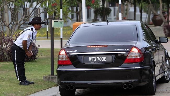 Probe... A car pulls up at the main gate of the gated community where pilot Zaharie Ahmad