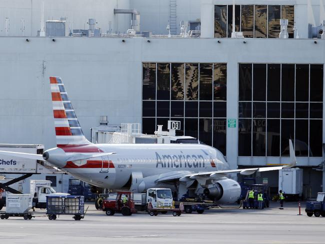An American Airlines Airbus A319 is parked at a gate at Miami International Airport, Monday, Nov. 6, 2017, in Miami. American Airlines and a subsidiary will pay $9.8 million in stock to settle claims that they failed to help disabled employees return to work. (AP Photo/Wilfredo Lee)