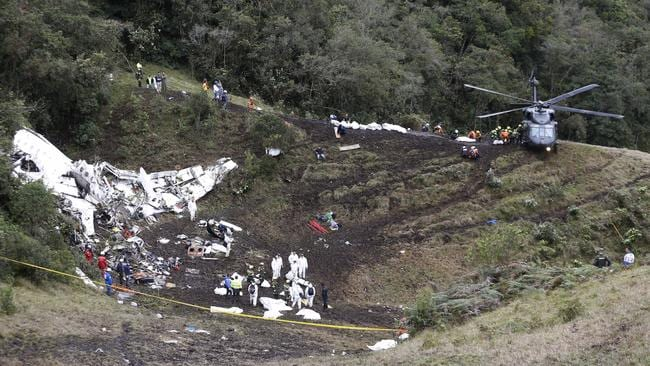 Rescue workers place the bodies of victims of an airplane crash in a helicopter.