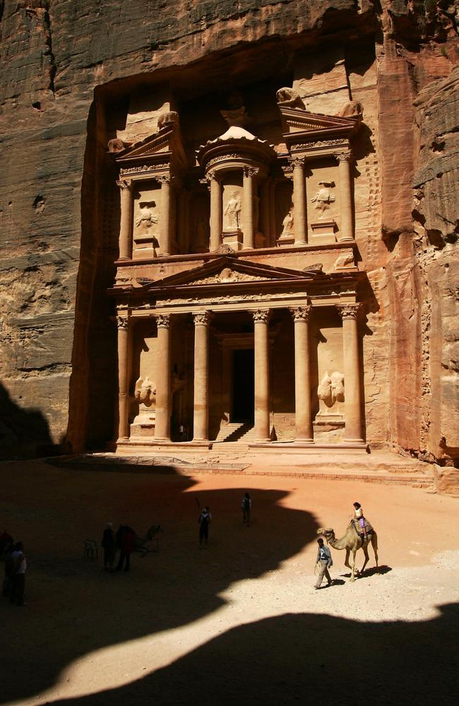 Tourists riding camels past the Treasury (al-Khazneh) building, the famous Petra monument.