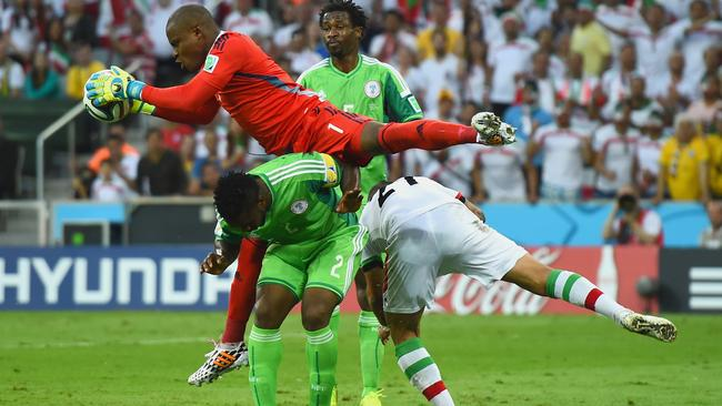 Vincent Enyeama bulldozes his way through two players to get to the ball.