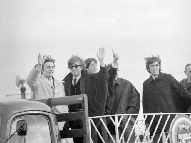 June 14, 1964: The Beatles and fill-in drummer Jimmie Nicol were put on a flat-bed truck so they could wave to the thousands of fans waiting to greet them at Essendon Airport. Picture: Herald Sun Image Library