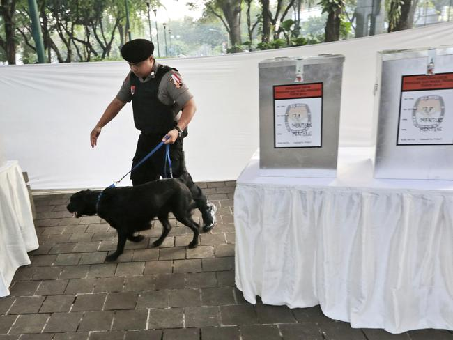 Security concerns ... a police officer leads a bomb-sniffing dog past ballot boxes as they conduct a security sweep at a polling station in Jakarta. Picture: Dita Alangkara