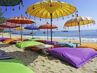 This image shows some colourful beach umbrellas and sand pillows in a pristine tropical beach bathed by the Bali sea.