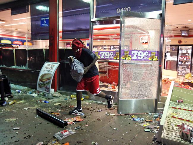 On the run ... a man flees a store in Ferguson, after riots broke out. Picture: AP /St. Louis Post-Dispatch, David Carson