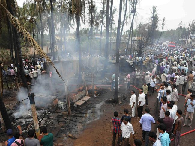 Smouldering ... Indian residents gather at the site of the gas explosion.