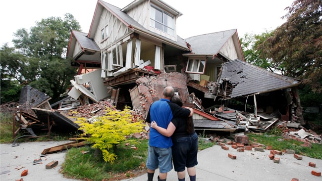 Murray and Kelly James look at their destroyed house in central Christchurch, New Zealand, Wednesday, Feb. 23, 2011. Tuesday's magnitude-6.3 temblor collapsed buildings, caused extensive other damage and killed dozens of people in the city. (AP Photo/Mark Baker)