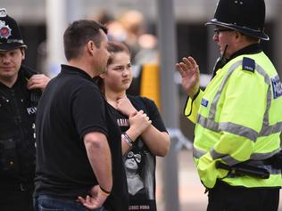 A police officer (R) talks with a man and a girl wearing a T-shirt of US singer Ariana Grande branded for the concert at the Manchester Arena in Manchester, northwest England on May 23, 2017 following a deadly terror attack at the concert at the venue the night before. Twenty two people have been killed and dozens injured in Britain's deadliest terror attack in over a decade after a suspected suicide bomber targeted fans leaving a concert of US singer Ariana Grande in Manchester. / AFP PHOTO / Oli SCARFF