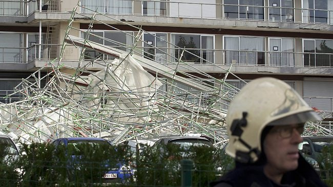 This picture taken on October 28, 2013 shows the debris on a parking lot next to an apartment building where a 13-floor high scaffolding came down due to the heavy winds in Merksem, Antwerpen. Nearly 300,000 homes were left without power in Britain and France today and trains and planes were cancelled as a fierce storm battered the region, leaving at least two people dead. AFP PHOTO / BELGA - KRISTOF VAN ACCOM