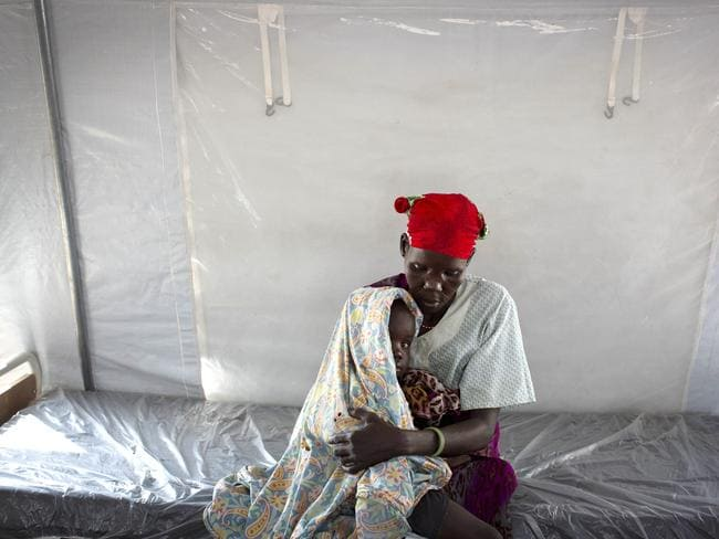 A woman holds her young son who is suffering from dehydration and unable to walk, at an emergency medical facility supported by UNICEF in Kuach, South Sudan. Picture: Kate Holt/UNICEF via AP