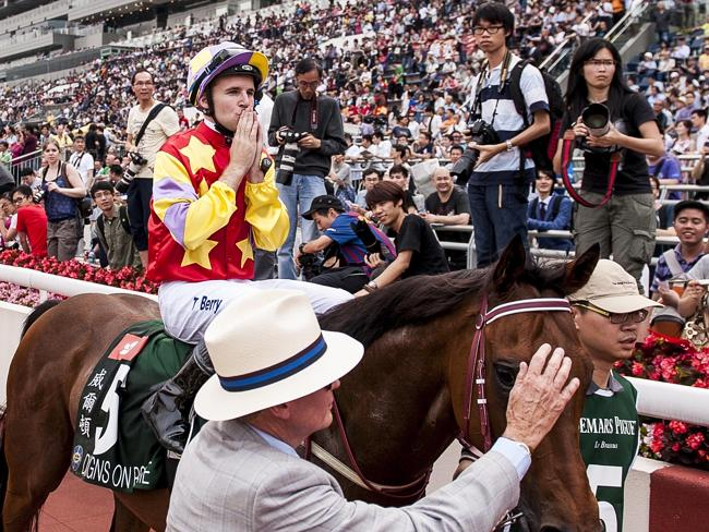 Tommy Berry makes a praying gesture aboard Designs On Rome as he returns to scale victorious. Picture: Getty Images