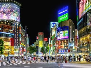People crossing the famous Shibuya crossing in Tokyo at night.