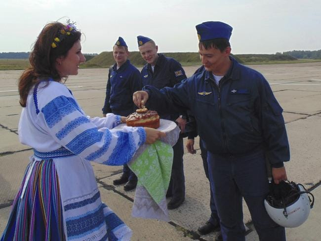 Russian military pilots are presented with traditional welcoming bread-and-salt as they arrive at an air base at undisclosed location in Belarus. Picture: AP