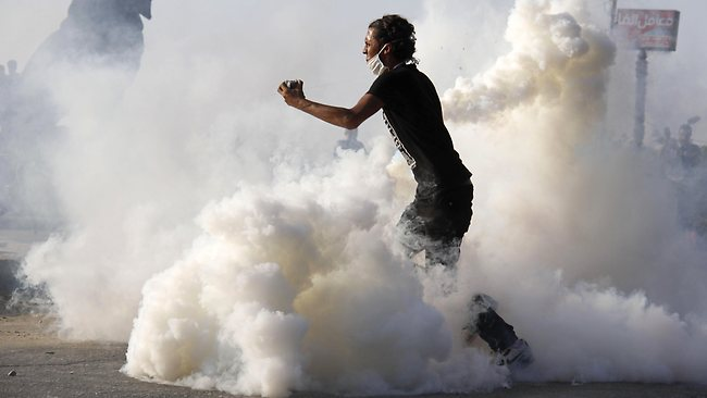 An Egyptian protester standing amid a fog of tear gas prepares to throw stones towards policemen during a demonstration against a film mocking Islam in Cairo. Picture: MOHAMMED ABDELMONEIM