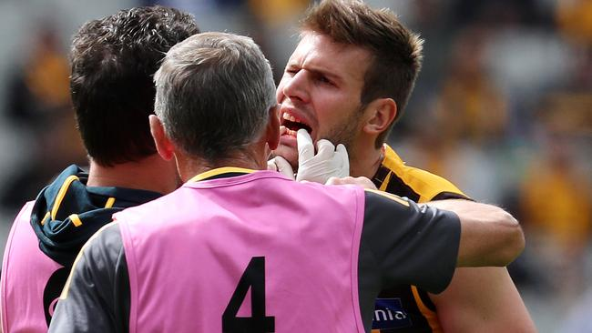 Grant Birchall gets checked out by Hawthorn medical staff. Picture: Michael Klein