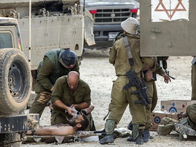 Fightback ... Israeli soldiers evacuate a wounded comrade at an army deployment area near Israel's border with the Gaza Strip.