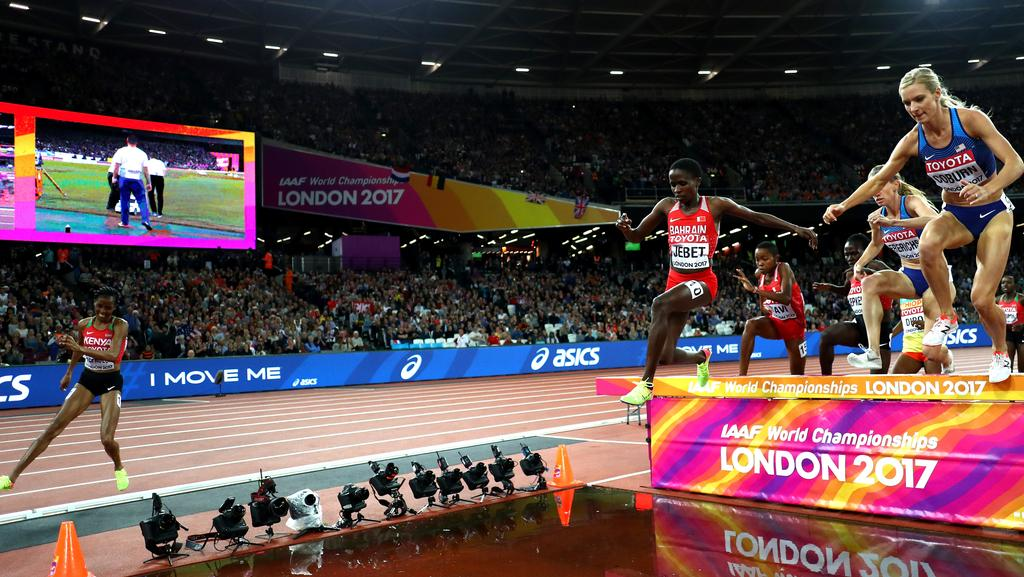 Beatrice Chepkoech of Kenya (L) misses the water jump in the Women's 3000 metres Steeplechase final.