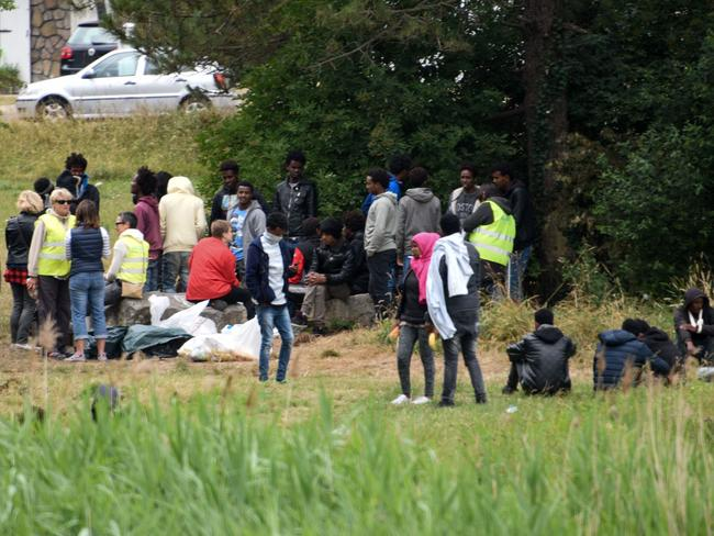 Migrants wait on a field near the ring road leading to the port of Calais in northern France. Picture: AFP