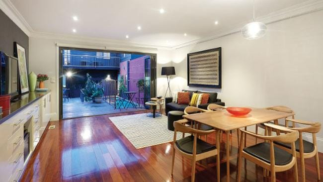 The open-plan kitchen, meals and family zone at 61 Merton St, Albert Park, leads to an outdoor entertaining deck and pool.