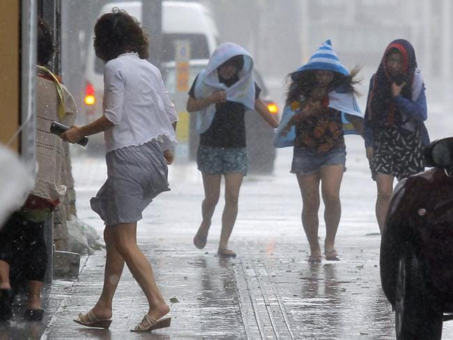 Women battle the strong winds and rain in Naha, Okinawa, southern Japan. Picture: AP Photo/Kyodo News