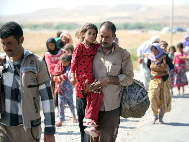 Exodus ... A displaced Iraqi man from the Yazidi community carries his daughter as they cross the Iraqi-Syrian border in northern Iraq. Kurdish forces from Iraq, Syria and Turkey worked together to break the siege of Mount Sinjar and rescue the displaced. Source: AFP
