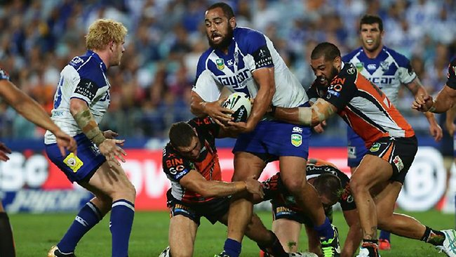 Bulldogs prop Sam Kasiano looks to get the ball away as Wests Tigers players try to bring him down. Picture: Brett Costello