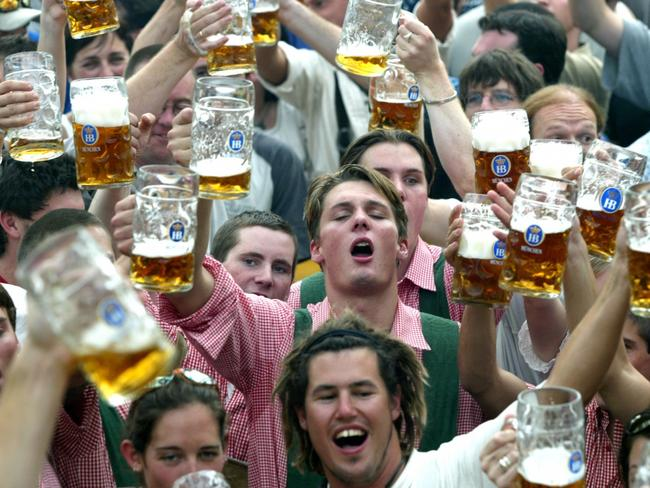Beer steins are raised by drinkers just after the opening of the Oktoberfest in Munich. Picture: AP