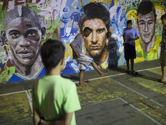 Boys practice freestyle soccer next to a mural depicting soccer players Mario Balotelli, Lionel Messi and Neymar Pic: Felipe Dana.