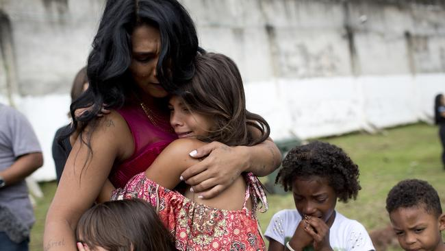Female inmate Rossana Goncalves with four of her five children cry as they reunite on the sidelines of competing in her jail's annual beauty contest. Picture: AP Photo/Silvia Izquierdo.