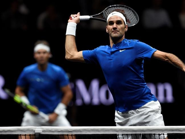 Switzerland's Roger Federer (R) hits a return in front of his teammate of team Europe, Spain's Rafael Nadal.