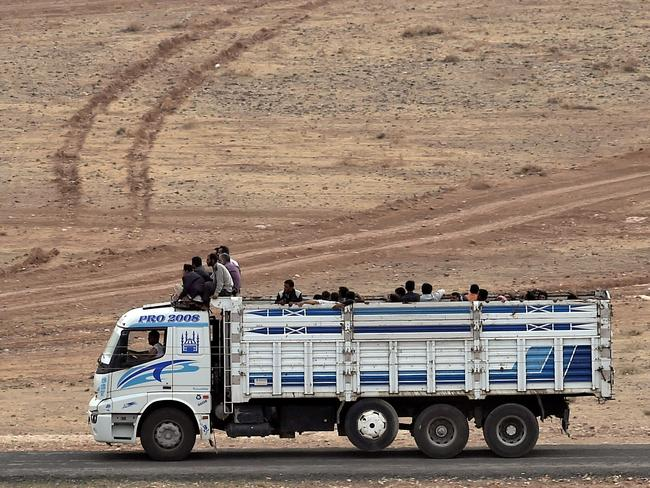 Heading out ... Syrian Kurds ride on a truck as they leave the Syrian town of Kobane. Picture: AFP